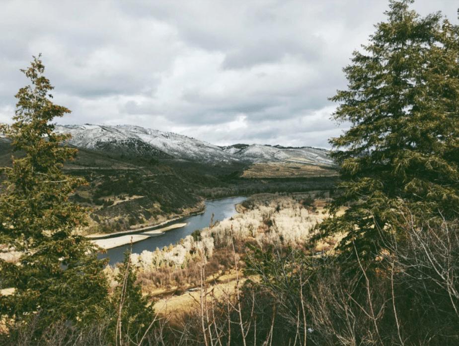 winter film foto van een berglandschap met bomen framing het beeld van besneeuwde bergen en een rivier