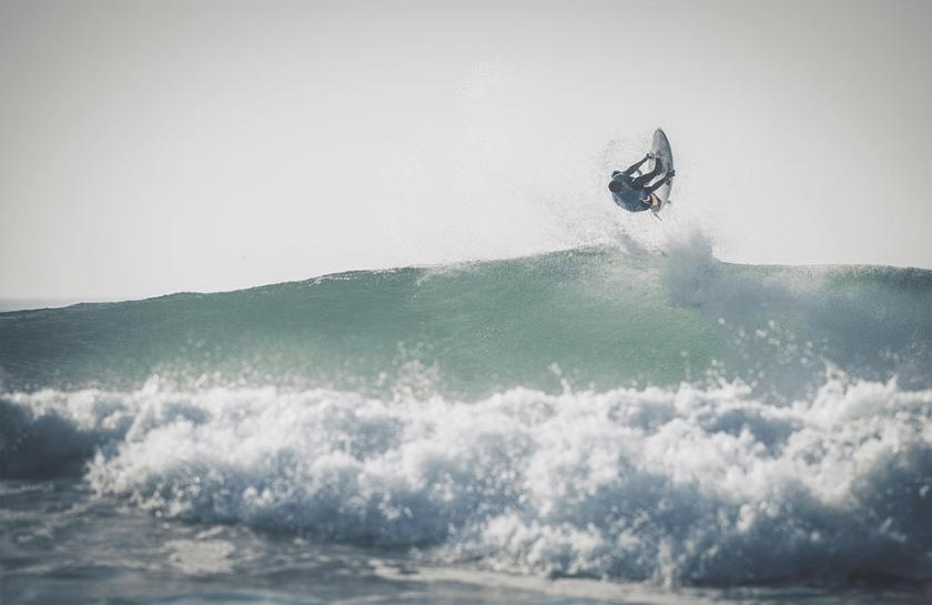 surfer die over een grote golf springt
