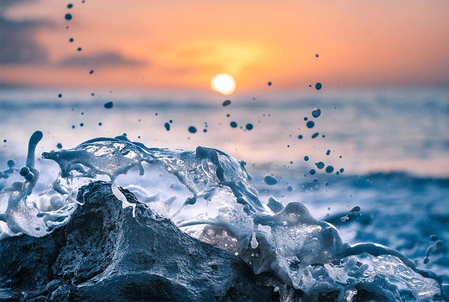 zeegolf spatten op een rots als de zonsondergang valt aan de horizon