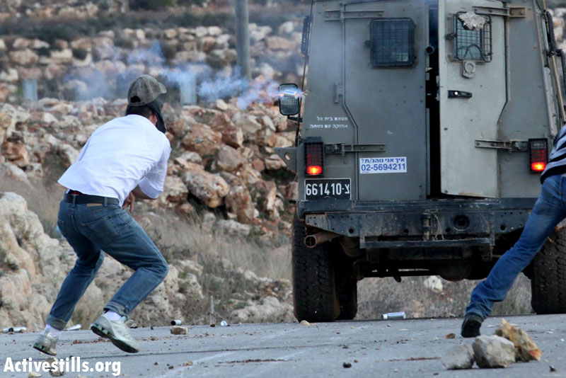 Mustafa Tamimi, a 28 year-old Palestinian from Nabi Saleh, seconds before an Israeli soldier shoots him in the face with a tear gas canister from a short distance, Nabi Saleh, December 12, 2011. (Haim Scwarczenberg)