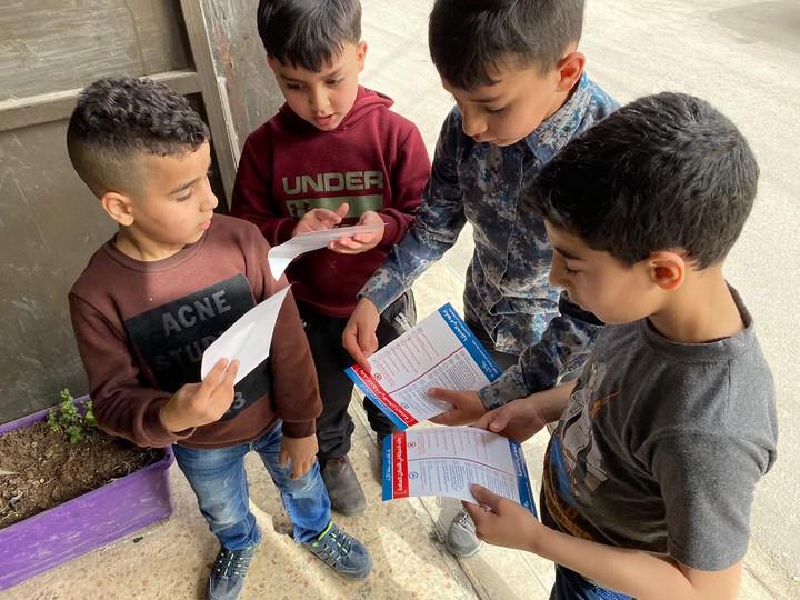 Children in Shuafat Refugee Camp hold flyers containing information on COVID-19, Jerusalem. (Kamel Ja'abri)