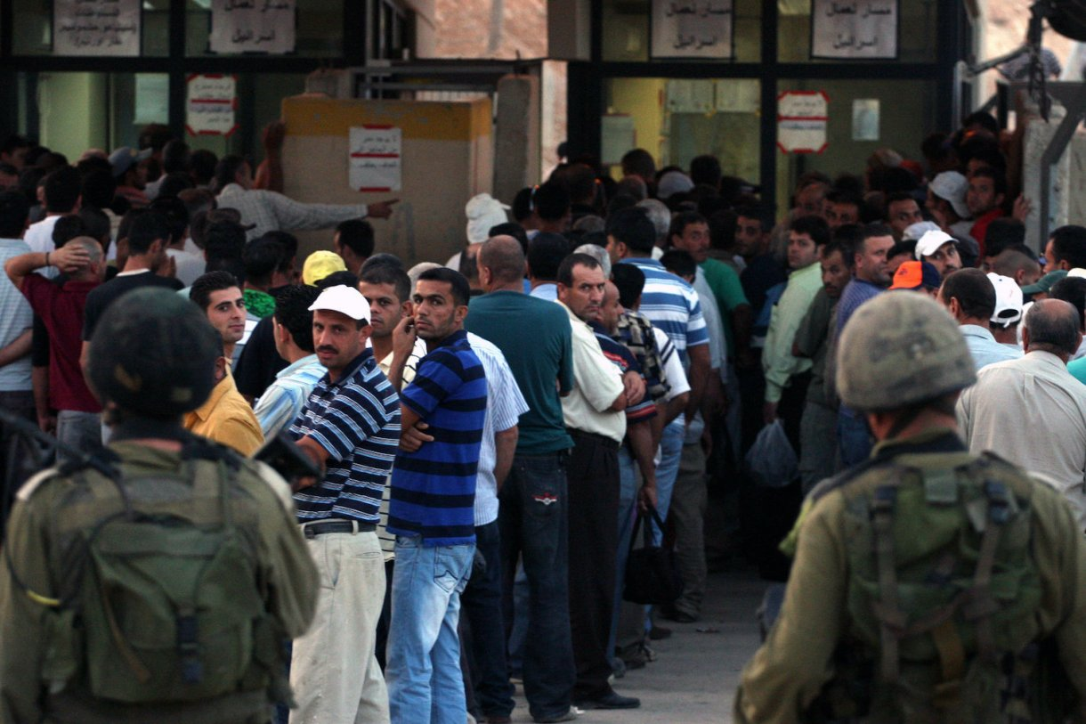Palestinian workers wait to cross the Isreali-controlled Ni'lin checkpoint, between the West Bank and the Jewish settlement of Modi'in Illit, as they head to work in Israel and nearby settlements on October 4, 2010. (Issam Rimawi/Flash90)