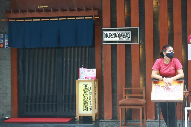 A worker at a Japanese restaurant in Bangkok's Silom area waits outside to greet customers.