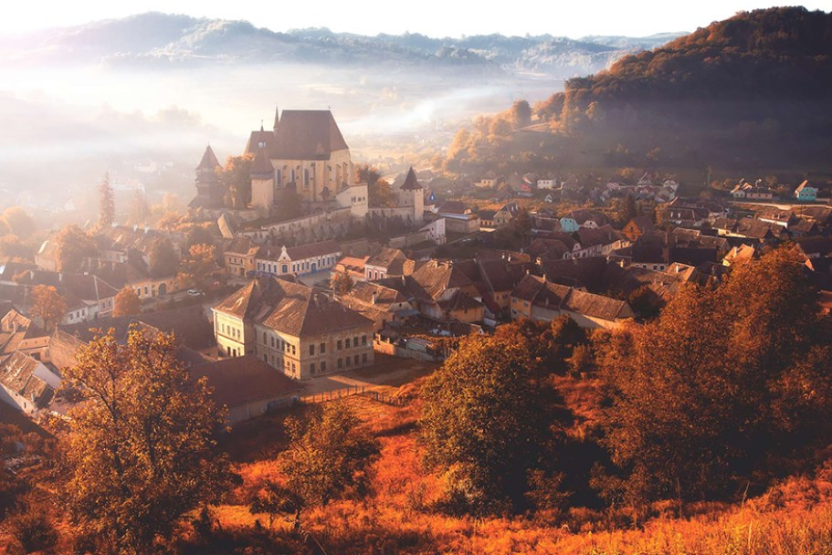 Overlooking the city of Transylvania, Romania with fog laying in the valley surrounded by autumn trees