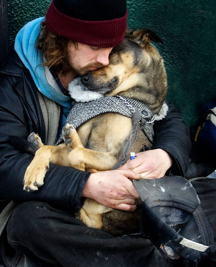 Homeless Man Sleeps In The Arms Of His Dog