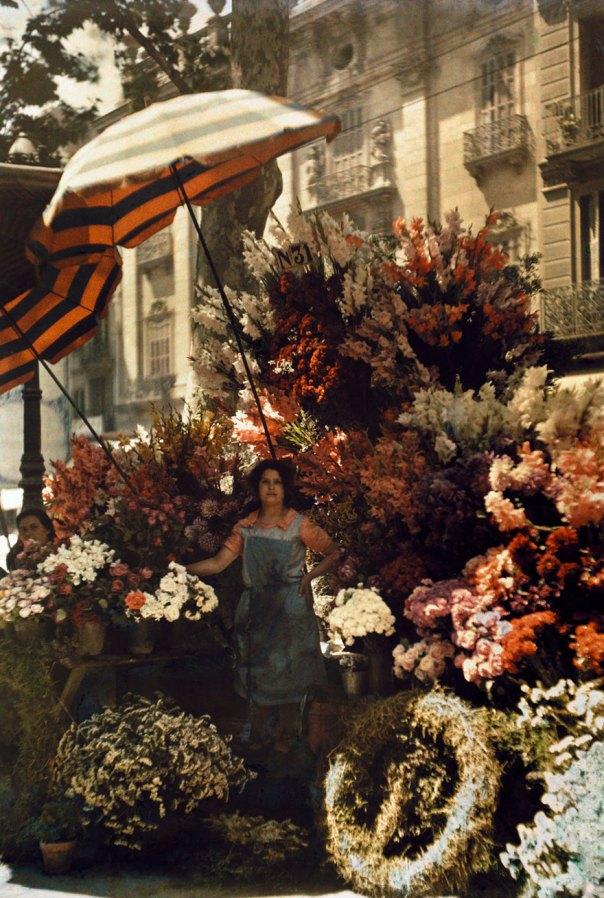 Una mujer se coloca delante de su puesto de flores en plena Rambla de Barcelona, España, marzo de 1929