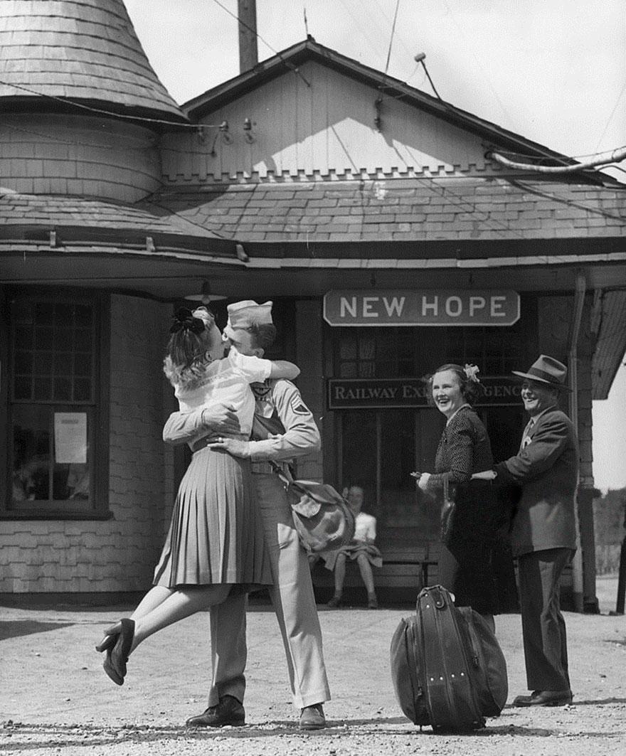 Una donna giovane solleva il piedi mentre abbraccia e bacia un soldato americano in uniforme Alla Stazione Ferroviaria, Connecticut 1945