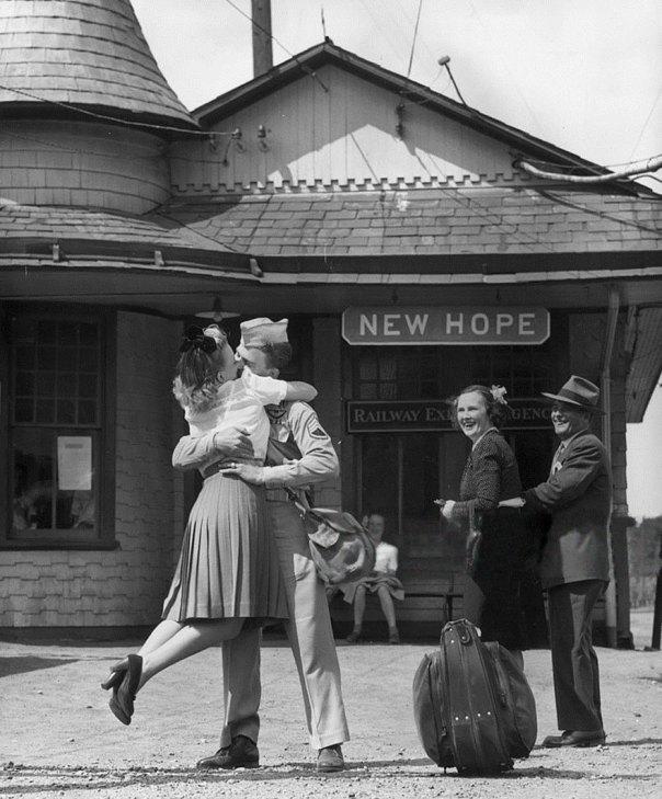 Una mujer joven levanta sus pies mientras abraza y besa Un uniformado a un soldado estadounidense en la estación de tren, Connecticut, 1945