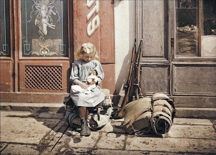 A Girl Holds A Doll Next To Soldiers' Equipment In Reims, France, 1917