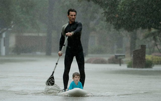 Alexendre Jorge Evacuates Ethan Colman, 4, From A Neighborhood Inundated By Floodwaters From Tropical Storm Harvey On Monday