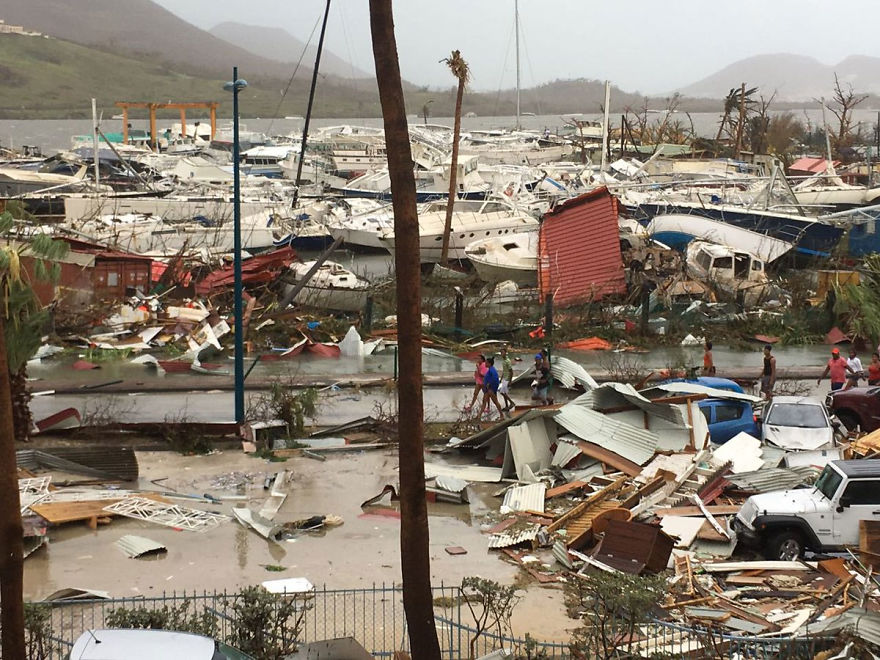 Locals Walk Through The Ruins Of A Harbour Area On The Island Of Saint Martin After The Hurricane Left It In Ruins