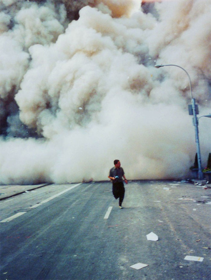 A Lone Man Runs Down Broadway As A Smoke And Dust Cloud Comes Up The Street From The Collapsing World Trade Center Buildings In New York September 11, 2001