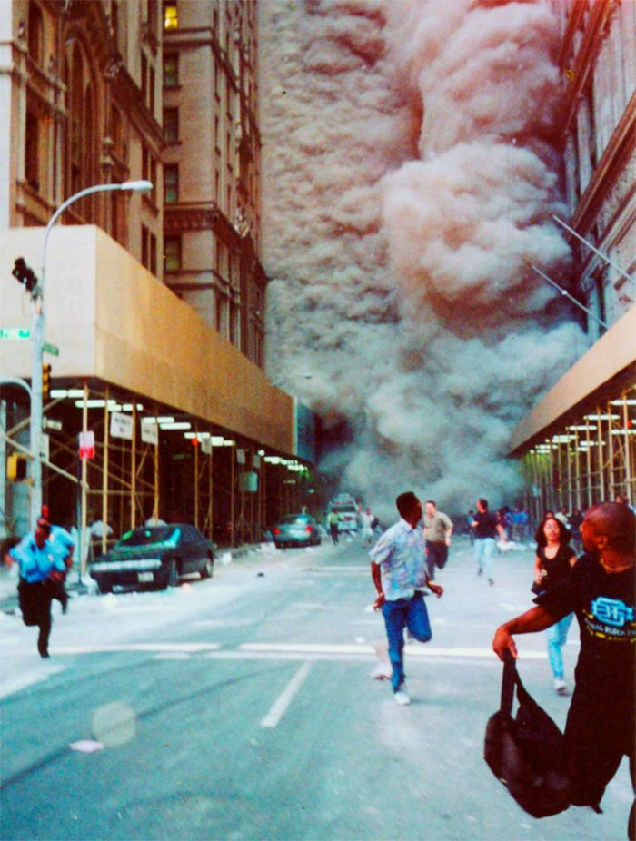 People Run Down Broadway As A Smoke And Dust Cloud Comes Up The Street From The Collapsing World Trade Center Buildings In New York