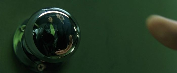 They Couldn't Hide The Camera In The Doorknob's Reflection Of This Scene Of The Matrix, So They Put A Coat Over It And A Half Tie To Match With Morpheus'