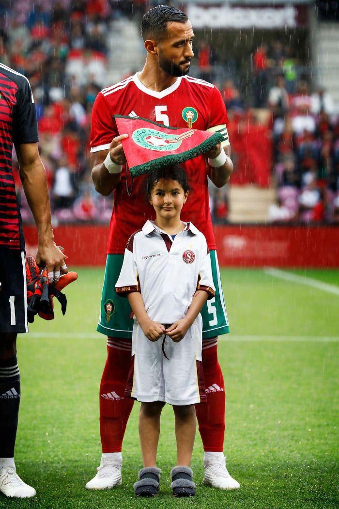 Jugador de fútbol marroquí Medhi Benatia Protección de una niña del Lluvia