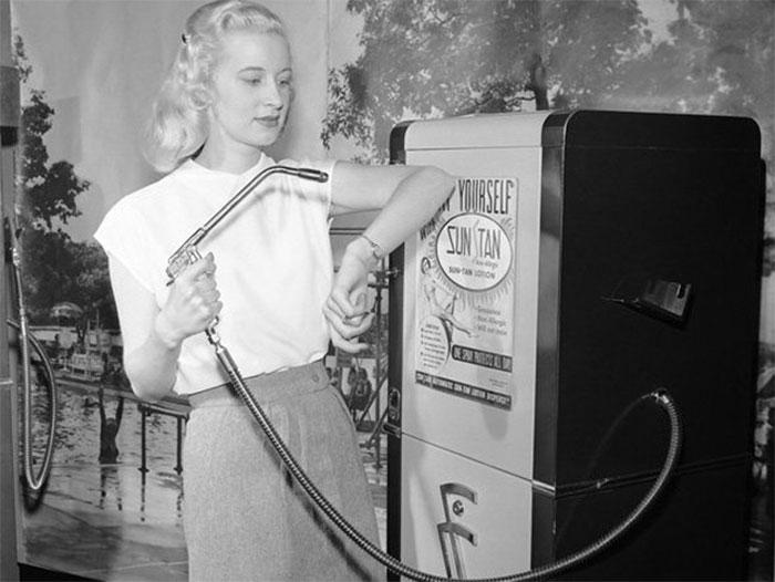 Mulher bronzeia usando uma máquina de venda automática de bronzeador, 1949