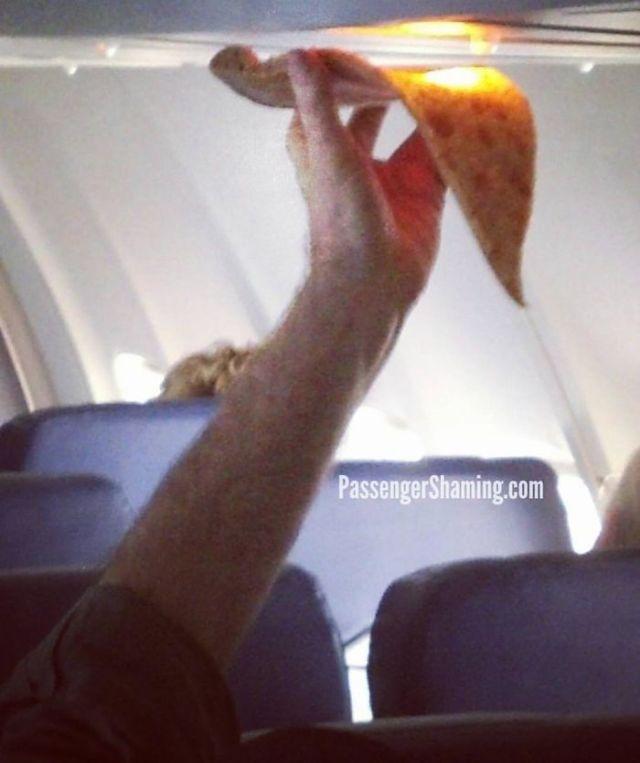 Un tipo tratando calentar su pizza con la calefacción del avión
