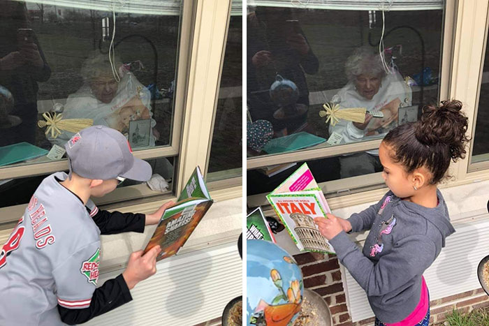 Grandchildren Reading To Their Great Grandmother Through The Window Of Her Nursing Home