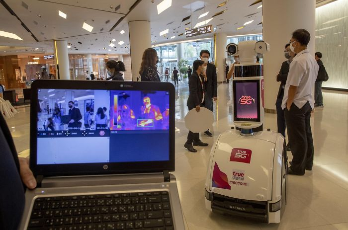 Mall In Bangkok Uses A Robot To Measure People's Body Temperatures As They Pass By
