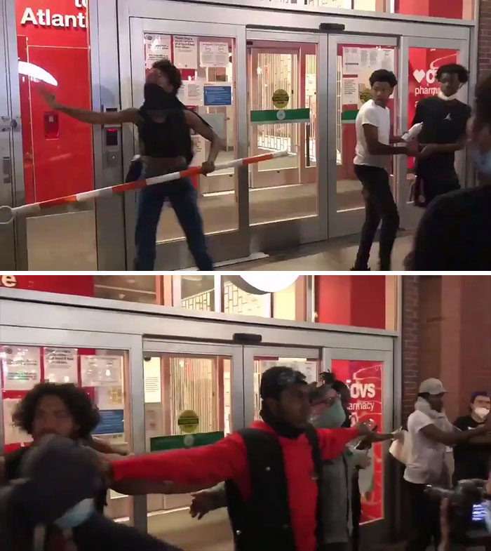 A Group Of People Forming A Human Barricade And Protecting The Store To Prevent People From Looting