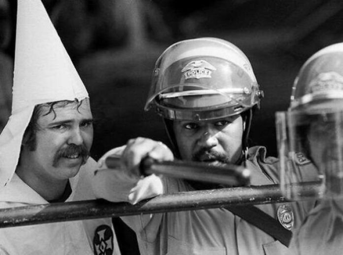 A Member Of The Ku Klux Klan Stands Behind A Police Officer For Protection, After A Mob Surrounded His Klan Rally In Austin Texas, 1983