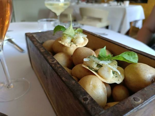 Little Bite Size Appetizer Served On A Box Of Uncooked Potatoes