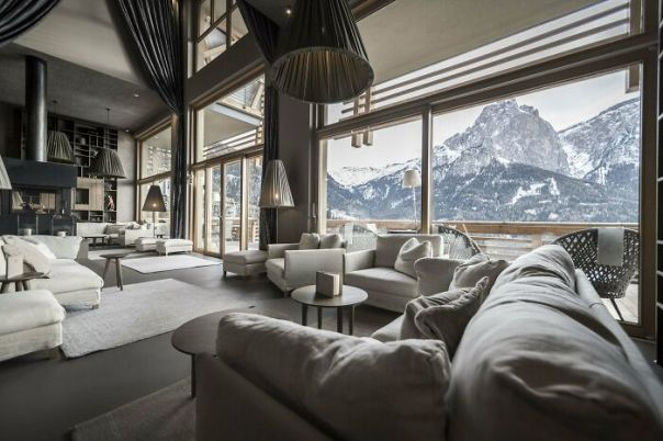 Tall And Spacious Hotel Lounge Centered Around A Fireplace With Stunning Views Of The Italian Dolomites, South Tyrol, Northern Italy