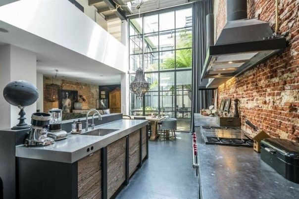 Kitchen Area Receives Lots Of Natural Light From The Two-Story Glass Wall In This Loft In Amsterdam