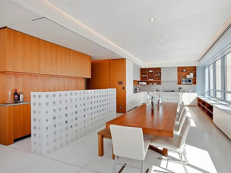 The kitchen is very minimalistic with its combination of white and wood accents and walls.