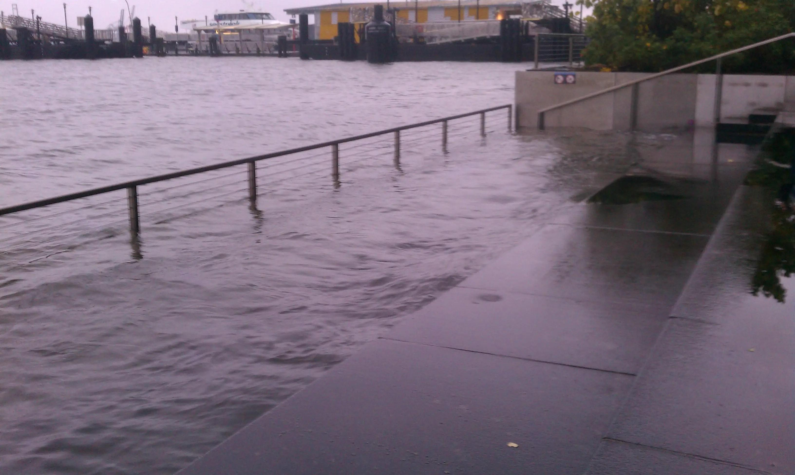 В результате наводнений Ист-Ривер конца стены утра улицы понедельник
