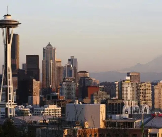 The Space Needle And Mount Rainier Are Pictured At Dusk In Seattle Washington March