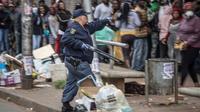 Un policier tient un fusil pour disperser la foule devant un supermarché, le 28 mars 2020 à Johannesburg, en Afrique du Sud [MARCO LONGARI / AFP]