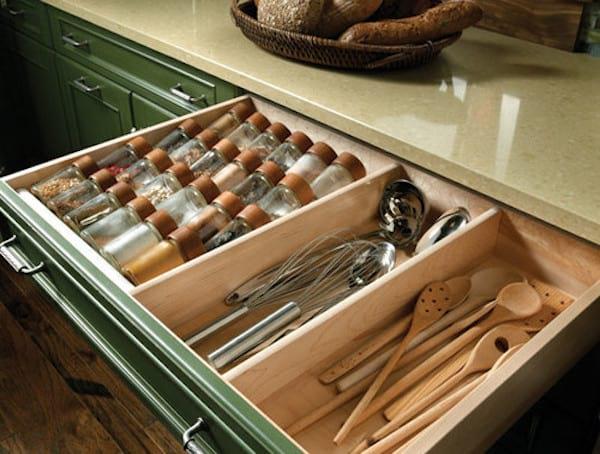 Grand tiroir vert qui sert de rangement pour ustensiles et épices