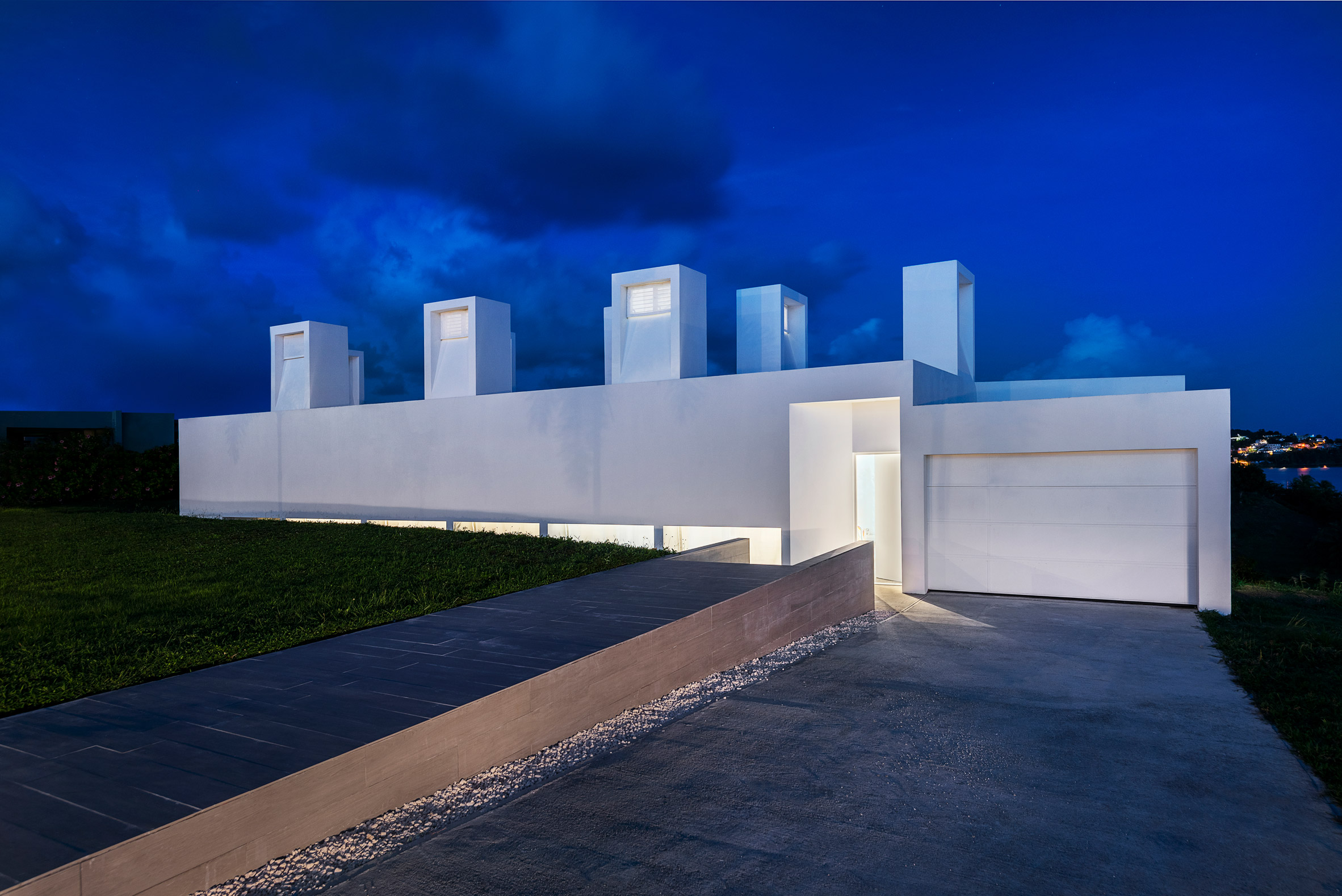 Nighttime exterior of concrete Casa Flores by Fuster + Architects