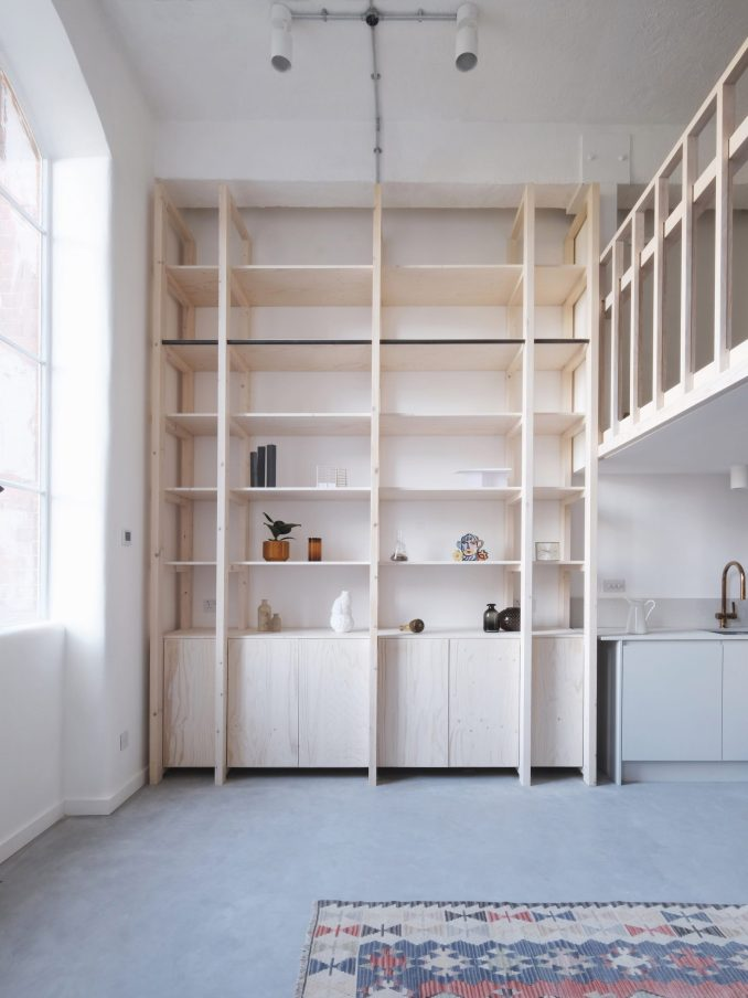 Double-height pine wood shelving unit from Bow Quarter interior by EBBA Architects