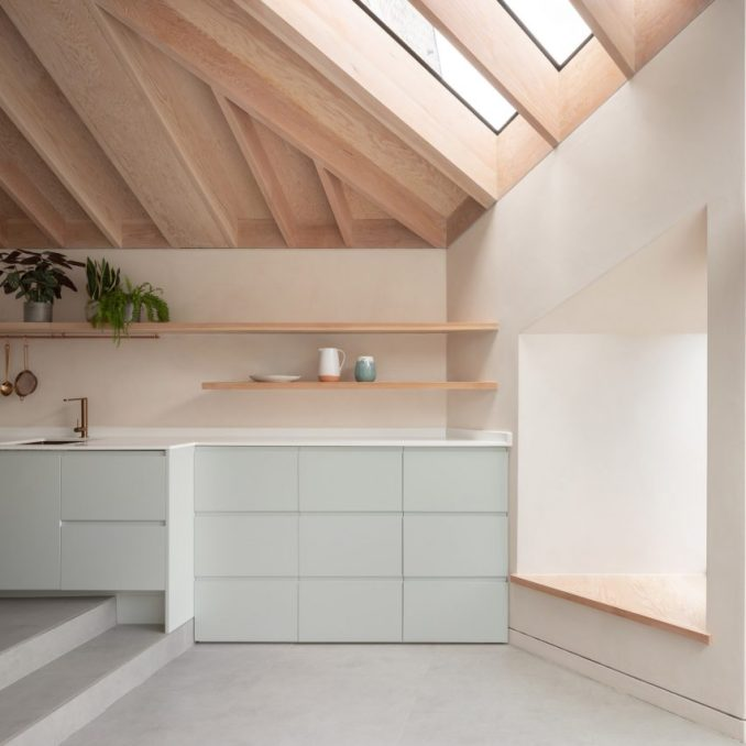 A residential kitchen with an exposed timber ceiling and duck-egg blue cabinetry
