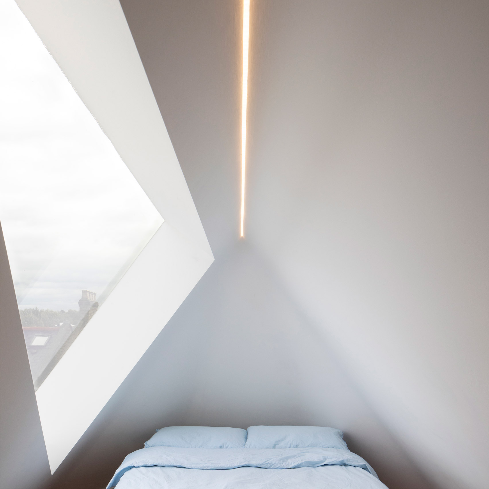 An angular white-walled bedroom with a skylight