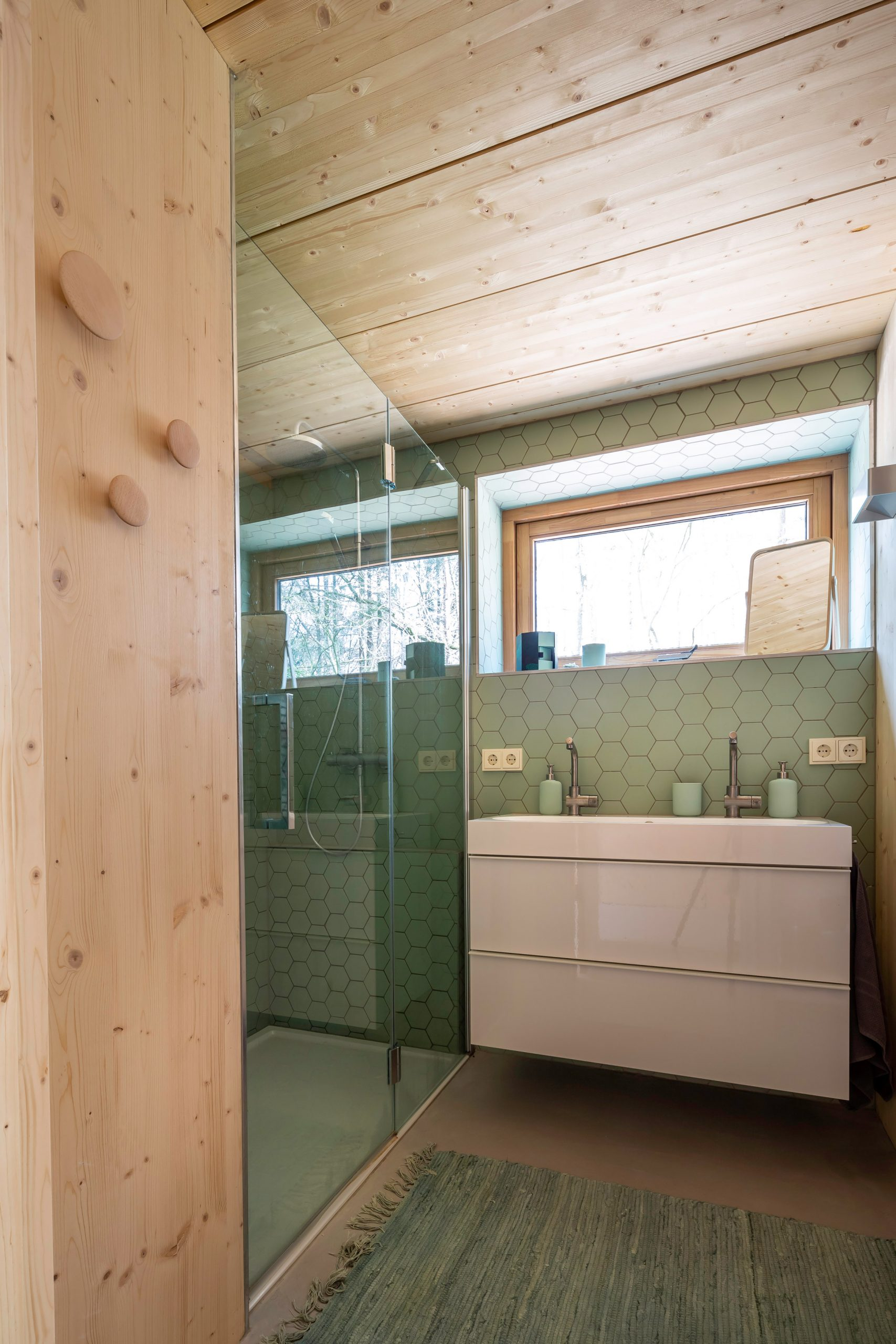 A wooden bathroom with green tiles