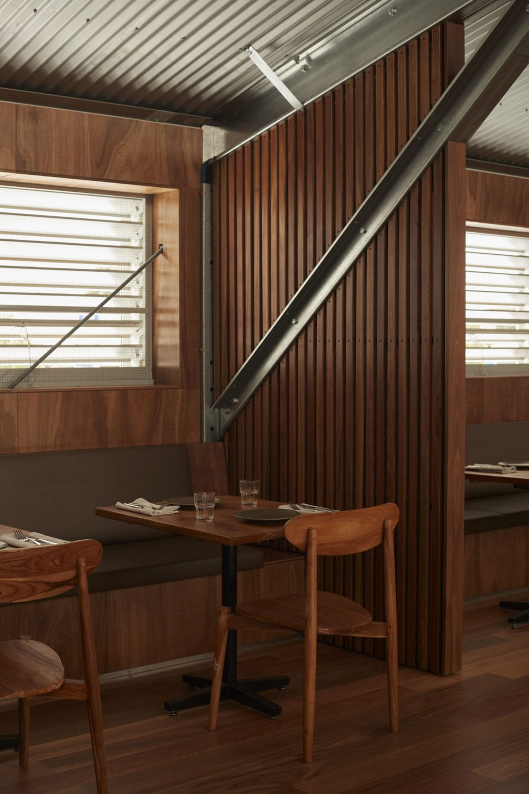Bench seating and corrugated steel ceiling in Three Blue Ducks restaurant in Melbourne Urbnsurf