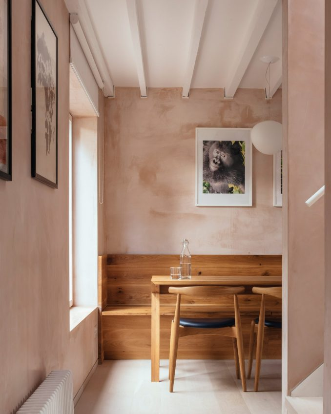 Oak dining table with light coming through a large window