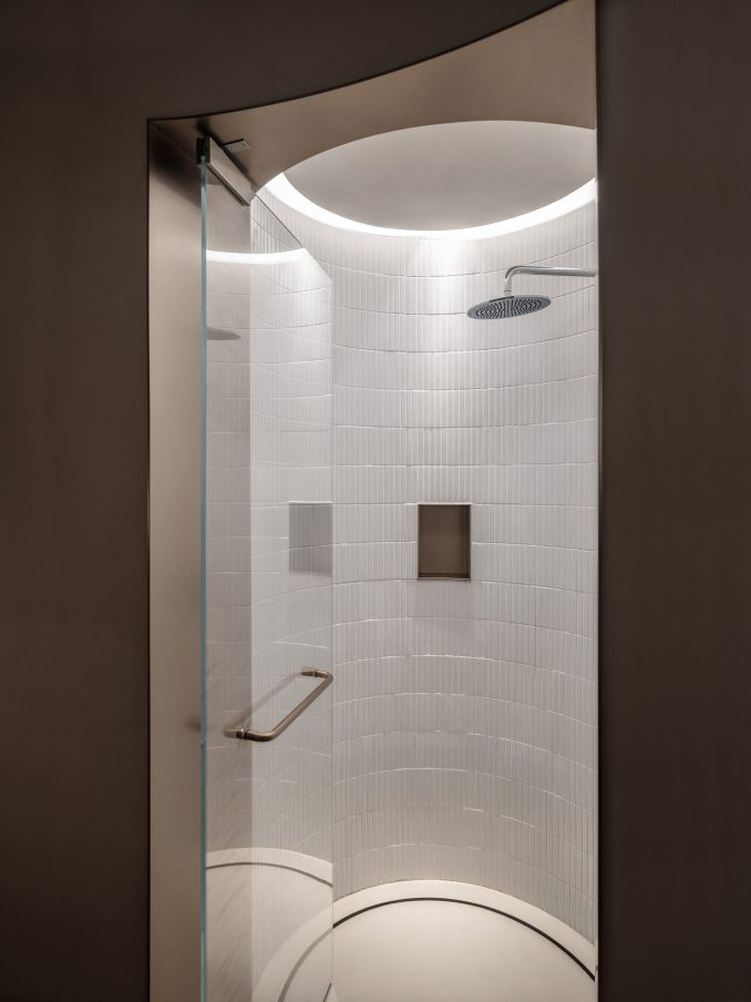 A glass door leads to a walk-in shower