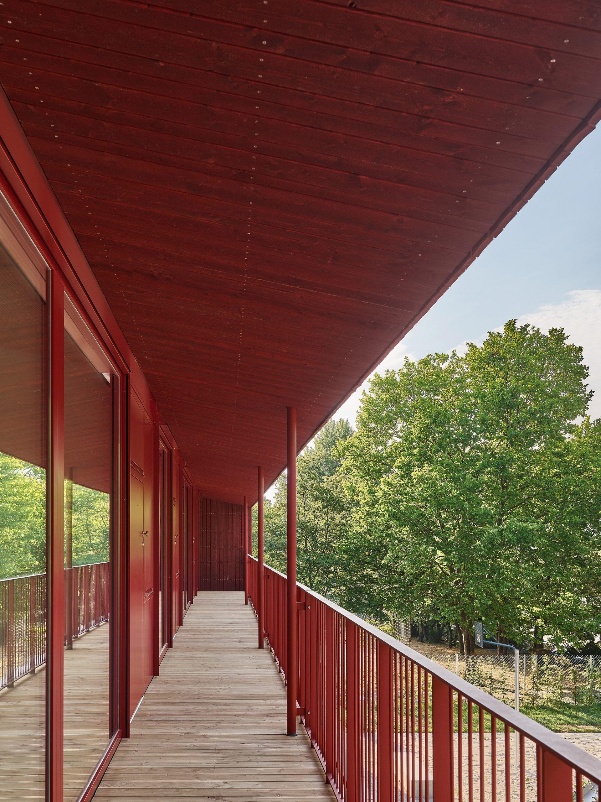 Red railings line the balcony terrace of daycare centre by Birk Heilmeyer und Frenzel Architekten