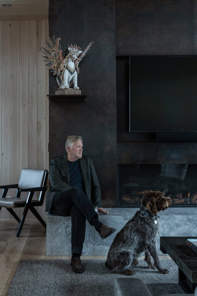 The architect by his blackened-steel fireplace