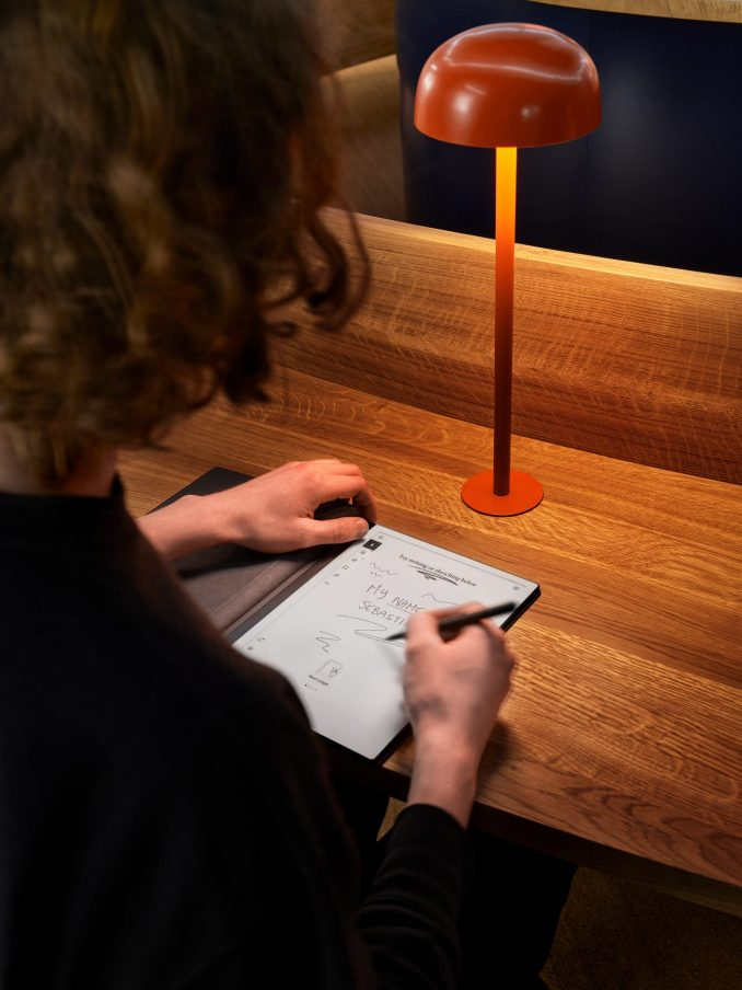 Person writing on reMarkable paper tablet at oak desk