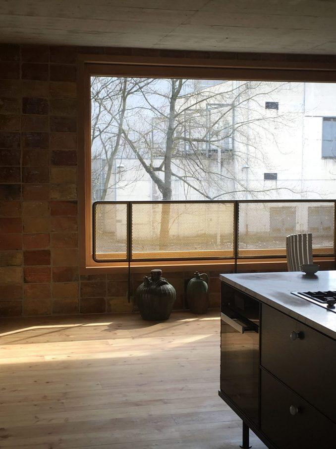 Kitchen with brick walls and wooden floors in interior by Philipp von Matt