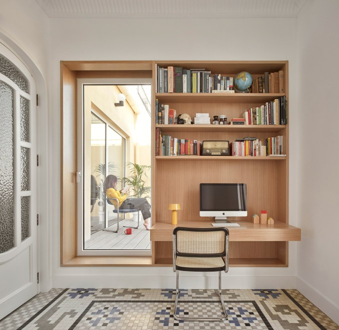 Home office with built-in wooden shelving and desk and door to terrace in Casa Cas 8