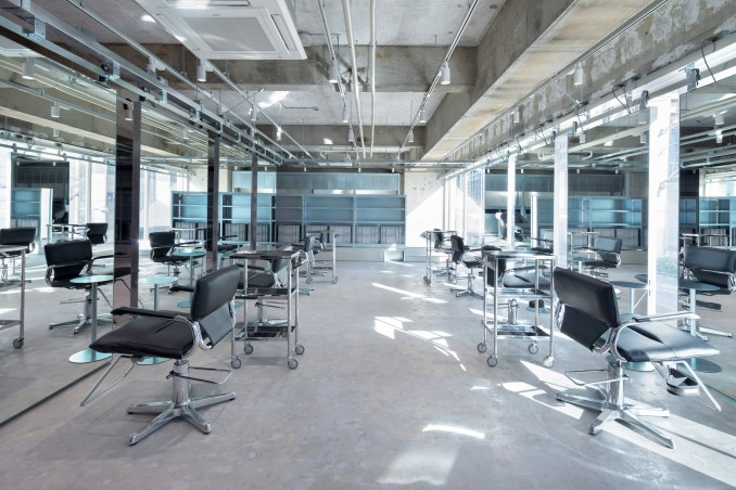 Hair dressing setups with suspended mirrors and concrete floors by Schemata Architects