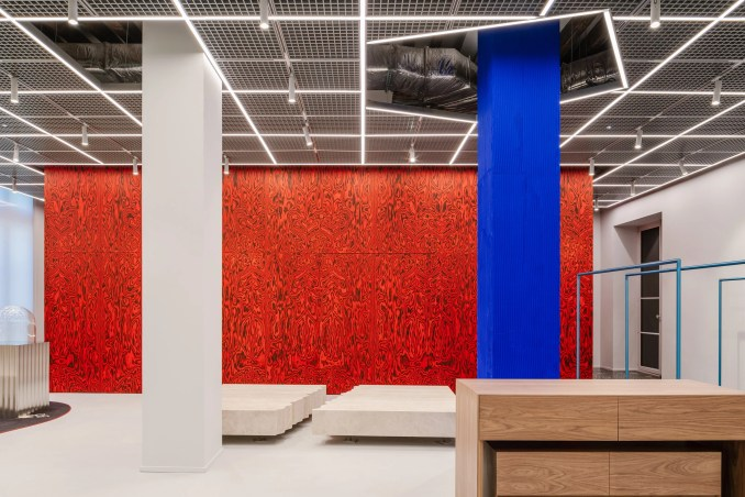 Red patterned wall with blue and white pillars in retail interior by AMO