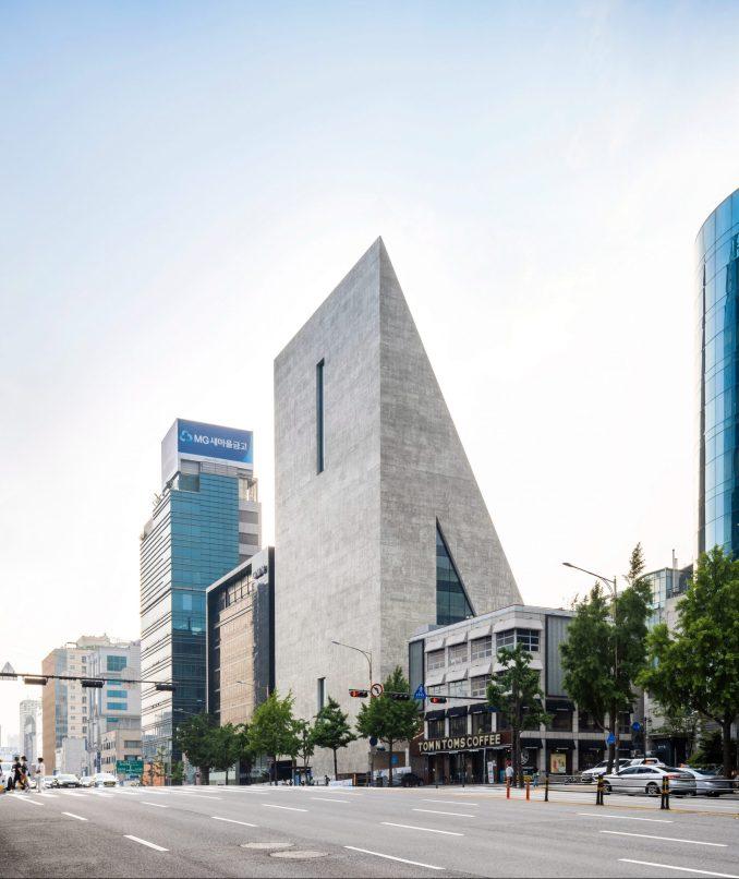 A triangular concrete building by Herzog & de Meuron