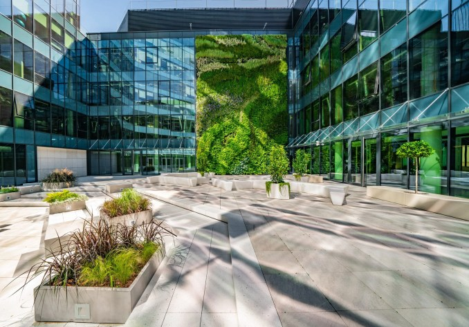 A photograph of glass building with green wall